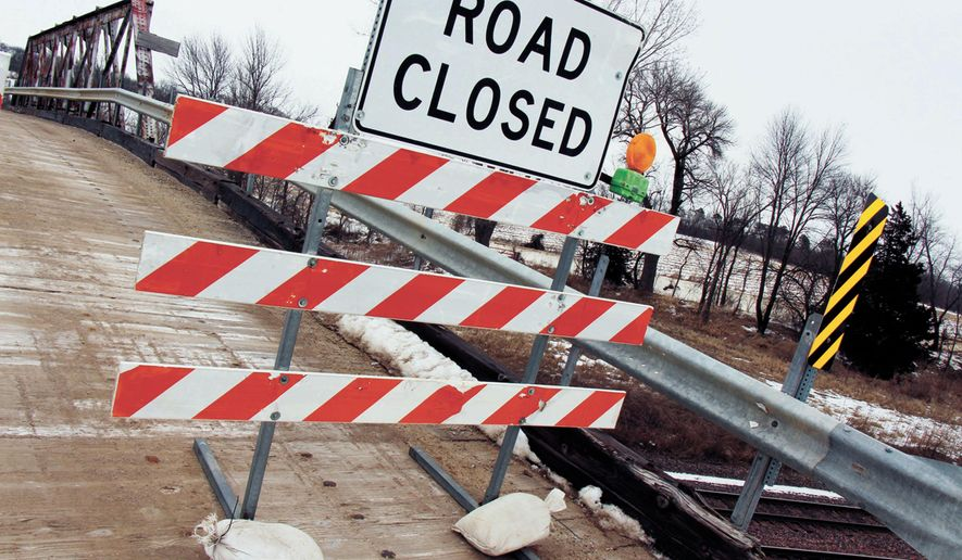 In this Feb. 16, 2015, photo, a road closed sign sits in front of a bridge in Quarry, Iowa. Marshall County engineer Paul Geilenfeldt says he closed the bridge Feb. 11 because he deemed it unsafe for public use. He says there is currently no timeline for the repair of the bridge, which is owned by Union Pacific Railroad, of Omaha, Nebraska. (AP Photo/Marshalltown Times-Republican, Bennet Goldstein)