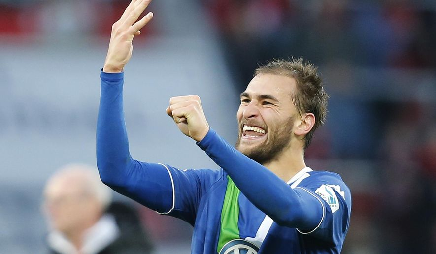 Wolfsburg's Bas Dost from the Netherlands holds up four fingers to show the number of goals he scored, at the end of the German first division Bundesliga soccer match between Bayer Leverkusen and VfL Wolfsburg in Leverkusen, Germany, Saturday, Feb. 14, 2015. (AP Photo/Frank Augstein)