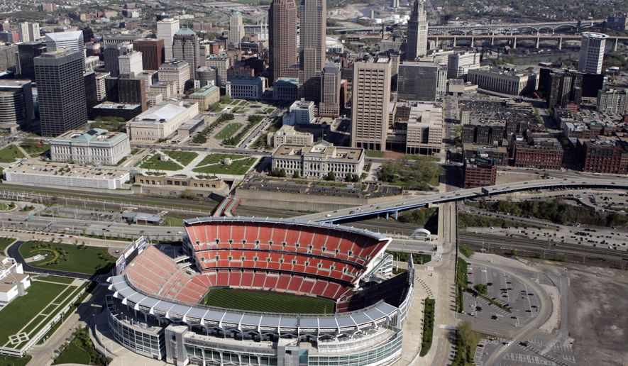 FILE - In this May 20, 2005 file photo, Cleveland Browns Stadium (now FirstEnergy Stadium), bottom, is seen north of downtown Cleveland. After voters last May approved a 20-year extension of the sin tax on cigarettes and alcohol that's projected to raise $26 million a year, county officials in northeast Ohio are still deciding how to split a sin tax among stadiums and arenas of Cleveland's professional sports teams. (AP Photo/Mark Duncan, File)