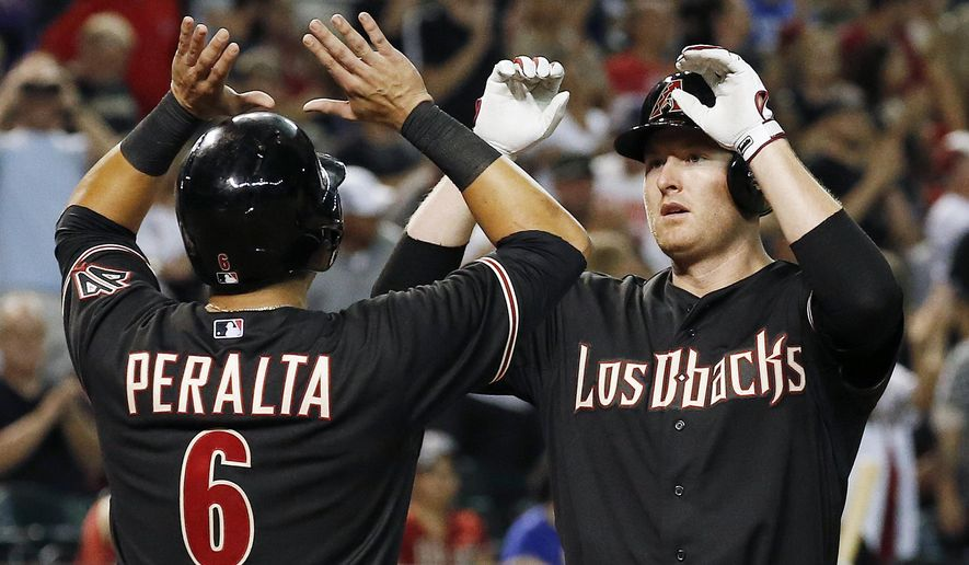FILE - In this Sept. 27, 2014, file photo, Arizona Diamondbacks' Mark Trumbo, right, celebrates his three-run home run against the St. Louis Cardinals with teammate David Peralta (6) during the seventh inning of a baseball game in Phoenix. Trumbo has won his salary arbitration case against the Diamondbacks and will get a $6.9 million salary this year instead of the team's $5.3 million offer. Howard Edelman, Margaret Brogan and Edna Francis made the decision Thursday, Feb. 19, 2015, a day after listening to arguments. (AP Photo/Ross D. Franklin, File)