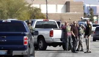 Las Vegas Metro Police officers and FBI agents stand in the street after a stand-off in Las Vegas Thursday, Feb. 19, 2015. Police arrested a man suspected of being involved in the road rage shooting of 44-year-old Tammy Meyers last week. (AP Photo/Las Vegas Sun/Steve Marcus)