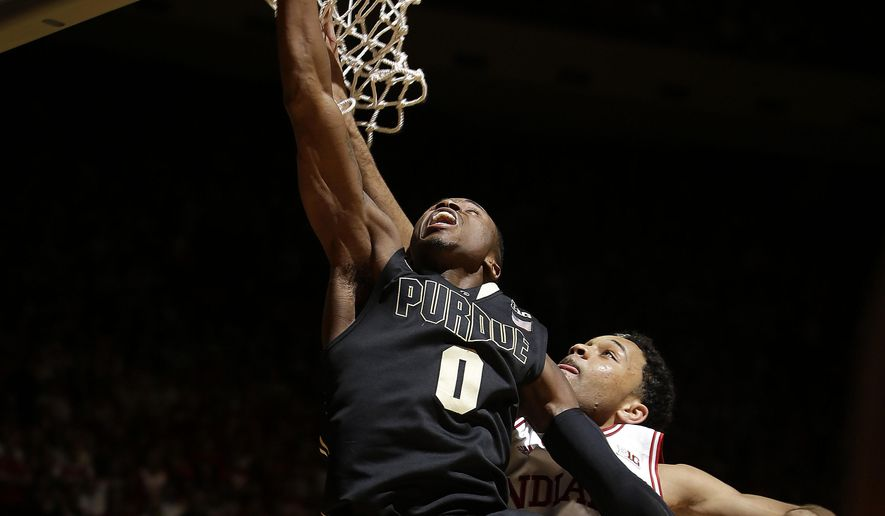 Purdue guard Jon Octeus, left, shoots in front of Indiana guard James Blackmon Jr. during the first half of an NCAA college basketball game in Bloomington, Ind., Thursday, Feb. 19, 2015. (AP Photo/AJ Mast)
