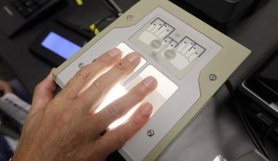Airline passenger Tom Reichert is digitally fingerprinted in the new Transportation Security Administration application site at the Detroit Metropolitan Airport in Romulus, Mich., Thursday, Feb. 19, 2015. (AP Photo/Carlos Osorio)