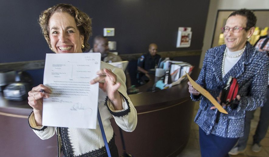 Suzanne Bryant is overcome with joy as she shows off her wedding license certificate as she walks out the Travis County clerk's office with Sarah Goodfriend on Thursday, Feb. 19, 2015 Austin, Texas. Travis County spokeswoman Ginny Ballard said the marriage occurred Thursday, though it wasn't immediately clear if the license has legal standing. The marriage followed a state District Court order instructing that officials not rely on Texas' unconstitutional prohibitions on same-sex marriage. (AP Photo/Austin American-Statesman, Ricardo B. Brazziell) AUSTIN CHRONICLE OUT, COMMUNITY IMPACT OUT; INTERNET AND TV MUST CREDIT PHOTOGRAPHER AND STATESMAN.COM; MAGS OUT
