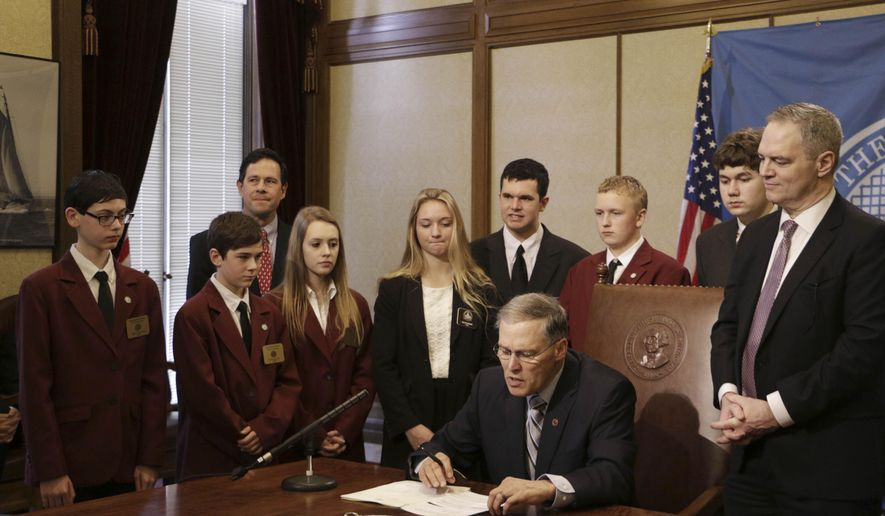 Washington Gov. Jay Inslee, seated, is joined by legislative pages and Senate and House budget writers as he prepares to sign a supplemental budget, Thursday, Feb. 19, 2015, in Olympia, Wash. The budget, which includes money for costs related to last year's wildfires, keeps the current two-year state budget balanced through June. (AP Photo/Rachel La Corte)