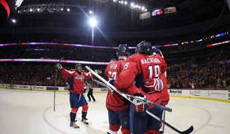In this picture taken with a fisheye lens, Washington Capitals center Nicklas Backstrom (19), of Sweden, celebrates his goal with Mike Green (52) and Alex Ovechkin, back left, of Russia, during the second period of an NHL hockey game against the Winnipeg Jets, Thursday, Feb. 19, 2015, in Washington. (AP Photo/Nick Wass)