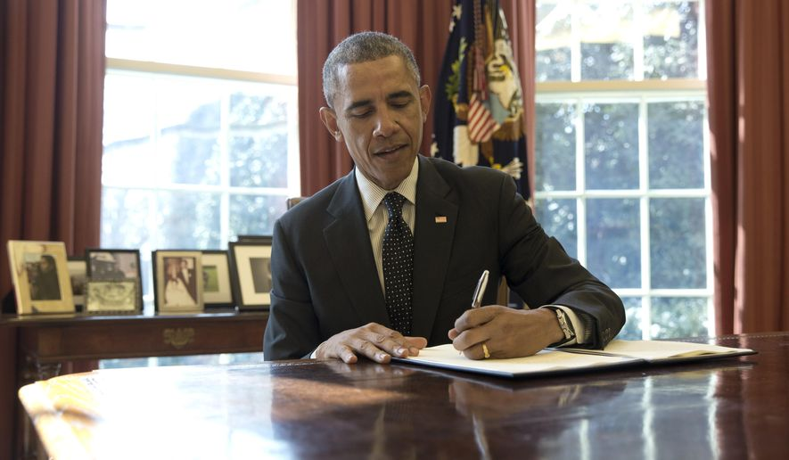 President Barack Obama signs documents in the Oval Office of the White House in Washington, Thursday, Feb. 19, 2015, designating BrownsCanyon National Monument in Colorado, a 21,000-acre site along the Arkansas River popular for whitewater rafting a national monument. (AP Photo/Carolyn Kaster)