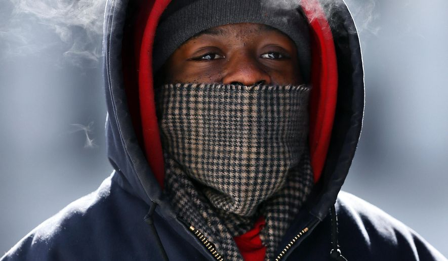Korey King's breath is visible as he walks in Detroit Thursday, Feb. 19, 2015. The National Weather Service says the temperature dropped to 5 below zero Thursday morning at Detroit Metropolitan Airport in Romulus, one degree below the previous Detroit record for the date from 1936. (AP Photo/Paul Sancya)