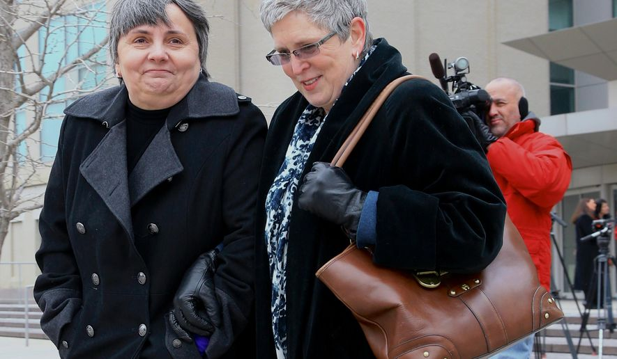 Susan Waters, left, and Sally Waters walk away from Federal Court in Omaha, Neb., after a hearing Thursday, Feb. 19, 2015. Terminally ill Susan and Sally are one of seven same-sex couples who had sued to block Nebraska's ban on gay marriage. In the hearing, U.S. District Judge Joseph Bataillon was asked to require the state of Nebraska to recognize same-sex marriages immediately while a lawsuit challenging the state's gay marriage ban proceeds, but the judge did not issue an immediate ruling. (AP Photo/Nati Harnik)