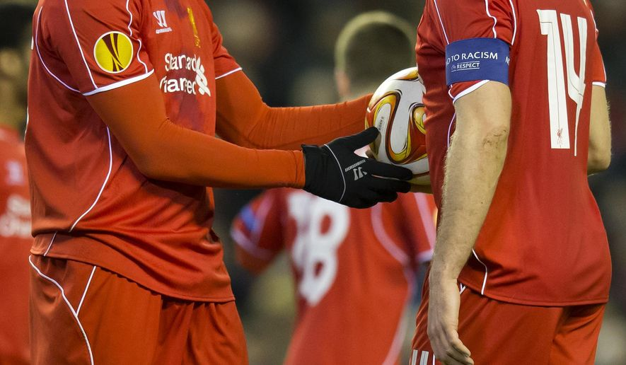 Liverpool's Mario Balotelli, left, takes the ball from captain Jordan Henderson before scoring a penalty during the Europa League Round of 32 soccer match between Liverpool and Besiktas at Anfield Stadium in Liverpool, England, Thursday, Feb. 19, 2015. (AP Photo/Jon Super)