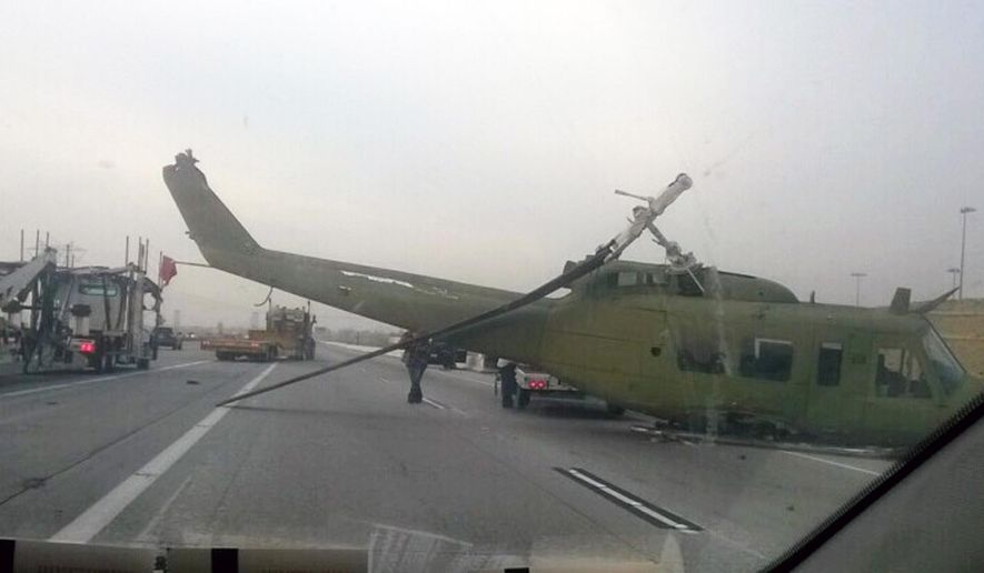 This photo provided by Amber Taylor shows a helicopter on the side of Interstate 15 near Fontana in San Bernardino, Calif., on Friday, Feb. 20, 2015. The helicopter being towed behind a truck struck a freeway overpass and crashed into lanes, hitting at least two vehicles in Southern California. (AP Photo/Amber Taylor)