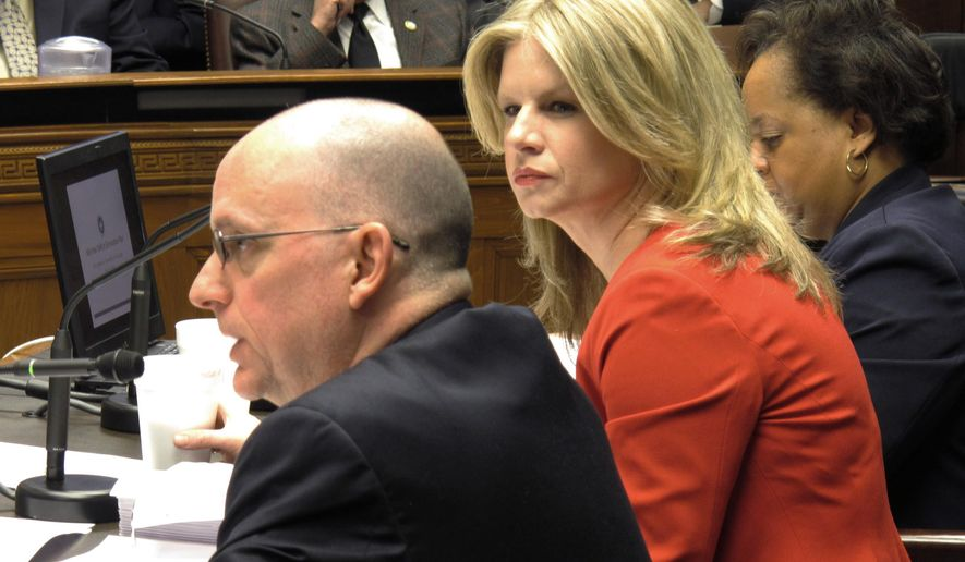 Commissioner of Administration Kristy Nichols, center, listens to Barry Dusse, director of the governor's Office of Planning and Budget, left, as he answers questions from state lawmakers in Baton Rouge, La. on Friday, Feb. 20, 2015 about the cuts planned to close this year's deficit. (AP Photo/Melinda Deslatte)