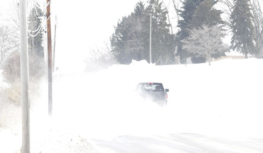 Strong winds made driving difficult as drifting snow cut visability on Broadway Ave. in Canton, Ohio Thursday, February 19, 2015. (AP Photo/ The Repository, Bob Rossiter)