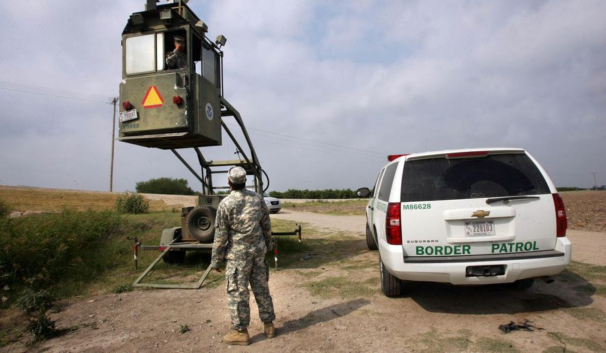 In this April 19, 2011 file photo, a member of the National Guard checks on his colleague inside a Border Patrol Skybox near the Hidalgo International Bridge in Hidalgo, Texas. (AP Photo/Delcia Lopez, File)