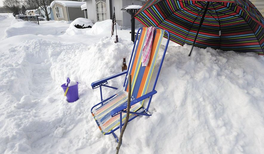 Beach accessories are displayed in the snow outside Erie County resident Brenda Taylor's house Thursday, Feb. 19, 2015, in Summit Township, Pa. (AP Photo/Erie Times-News, Greg Wohlford) MAGAZINES OUT; MANDATORY CREDIT