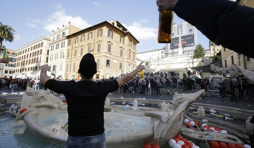 """Bottles and beer cans float in the water as Feyenoord's fans start causing troubles near the fountain called """"Barcaccia"""", made by Pietro Bernini and his son Gian Lorenzo in 1627,  at the Spanish steps, in downtown Rome, prior to the Europa League soccer match between Roma and Feyenoord, Thursday, Feb. 19, 2015. The supporters rampaged through Rome's famous Piazza di Spagna on Thursday, clashing with police and injuring several officers after throwing flares and other objects. The square and the iconic Spanish Steps were left covered with beer bottles and other litter, while the recently-restored Barcaccia fountain was also damaged. (AP Photo/Gregorio Borgia)"""