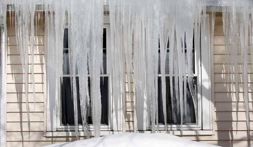"""Icicles hang from the roof of a house in Quincy., Mass., Friday, Feb. 20, 2015. With a wintry mix on the way this weekend and another larger storm possibly on the horizon, """"ice dams"""" are a growing concern for New England homeowners. Massachusetts Gov. Charlie Baker and other state leaders have been urging residents to clear off excess snow from roofs or hire professionals to do it. (AP Photo/Michael Dwyer)"""