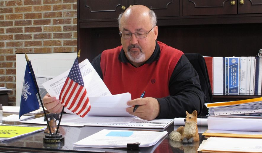 Marion County Administrator Tim Harper sits at his desk on Wednesday, Feb. 11, 2015, in Marion, S.C. Harper said his county has struggled as South Carolina lawmakers have failed to give the full amount prescribed by law to a fund supposed to give money back to counties for performing state functions. (AP Photo/Jeffrey Collins)