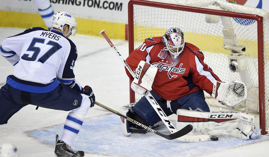 Washington Capitals goalie Braden Holtby (70) stops the puck in front of Winnipeg Jets defenseman Tyler Myers (57) during the third period of an NHL hockey game, Thursday, Feb. 19, 2015, in Washington. The Capitals won 5-1. (AP Photo/Nick Wass)