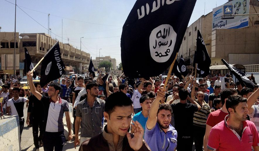 In this June 16, 2014, file photo, demonstrators chant pro-Islamic State group, slogans as they carry the group's flags in front of the provincial government headquarters in Mosul, 225 miles (360 kilometers) northwest of Baghdad. (AP Photo, File)