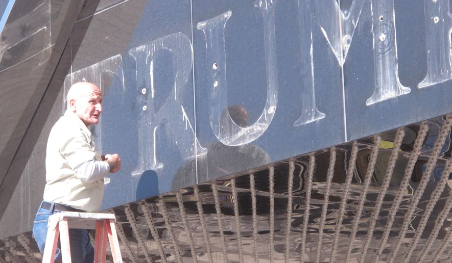 """In this photo taken Oct. 6, 2014, a worker removes the """"Trump"""" name from the Trump Plaza casino in Atlantic City, N.J. A bankruptcy court judge sided with Donald and Ivanka Trump on Friday, Feb. 20, 2015, ruling that they can move forward with a lawsuit seeking to strip the family name from Atlantic City's Taj Mahal casino. Trump Entertainment Resorts, with which Donald Trump is no longer affiliated, has stripped the Trump name from most of Trump Plaza, which closed on Sept. 16, but is fighting to be able to use it at the Taj Mahal, its lone remaining casino. (AP Photo/Wayne Parry)"""