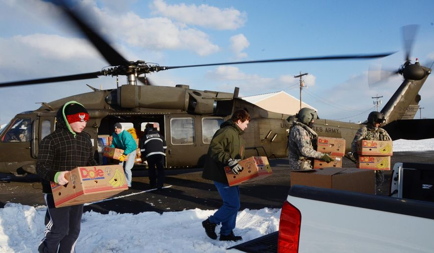 In this photo taken on Thursday, Feb. 19, 2015, provided by the Virginia Guard Public Affairs Office, a Virginia Army National Guard aviation crew from the Sandston-based 2nd Battalion, 224th Aviation Regiment delivers food, mail and medicine to iced-in Tangier Island, Va. The 1.2 square mile island has been iced in since freezing temperatures blanketed the commonwealth last week, making routine seaport deliveries impossible. The state active duty mission was authorized by Governor Terry McAullife's Declaration of Emergency issued on Monday and coordinated by the Virginia Department of Emergency Management with Maryland public safety officials and the United States Coast Guard.  (AP Photo/Virginia Guard Public Affairs Office, Staff Sgt. Terra C. Gatti)