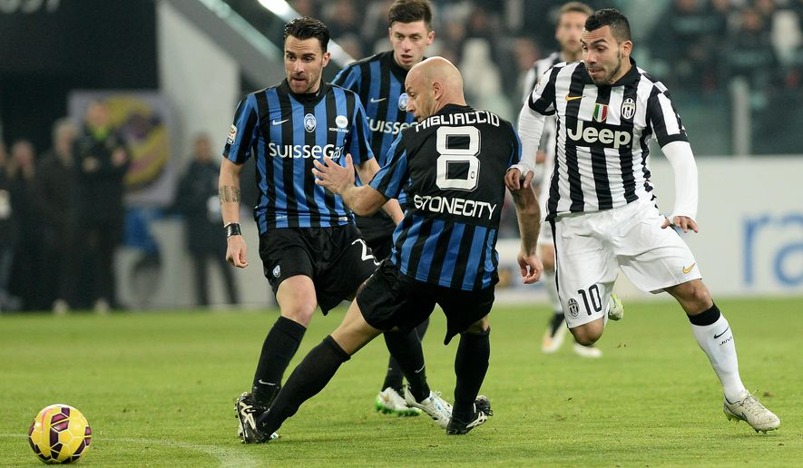 Juventus' Carlos Tevez, right, challenges for the ball with Atalanta' Giulio Migliaccio during a Serie A soccer match between Juventus and Atalanta at the Juventus stadium, in Turin, Italy, Friday, Feb. 20, 2015. (AP Photo/ Massimo Pinca)