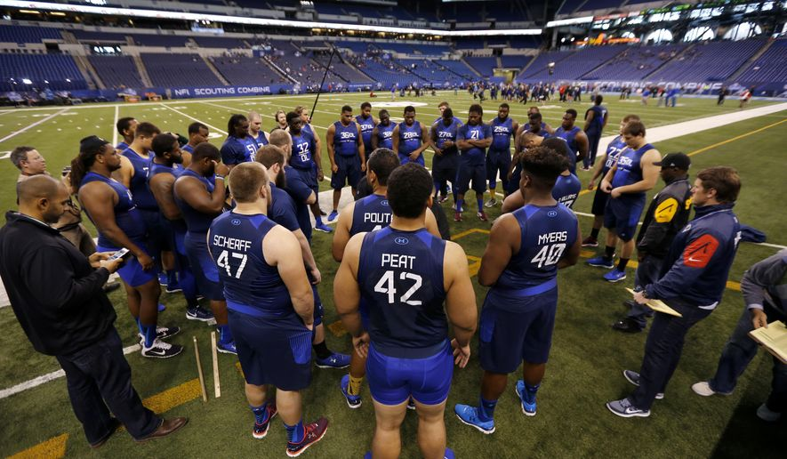 Offensive linemen gather before being measured at the NFL football scouting combine in Indianapolis, Friday, Feb. 20, 2015. (AP Photo/Julio Cortez)