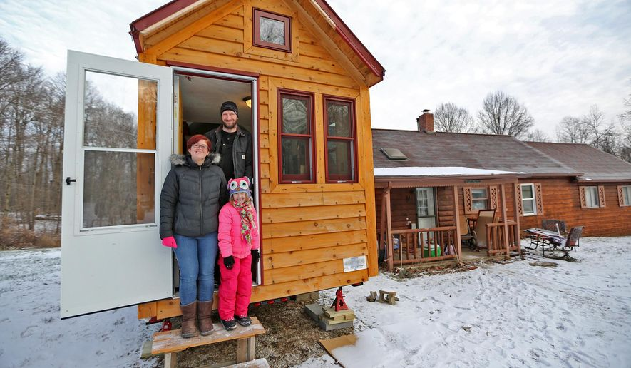 In this photo taken on Thursday, Jan. 8, 2015, Angel Tyra, left, her husband Cori Cox and their daughter, Amelia Cox, 8, stand in the doorway of their tiny house in Clay County, Ind. (AP Photo/The Indianapolis Star, Kelly Wilkinson)
