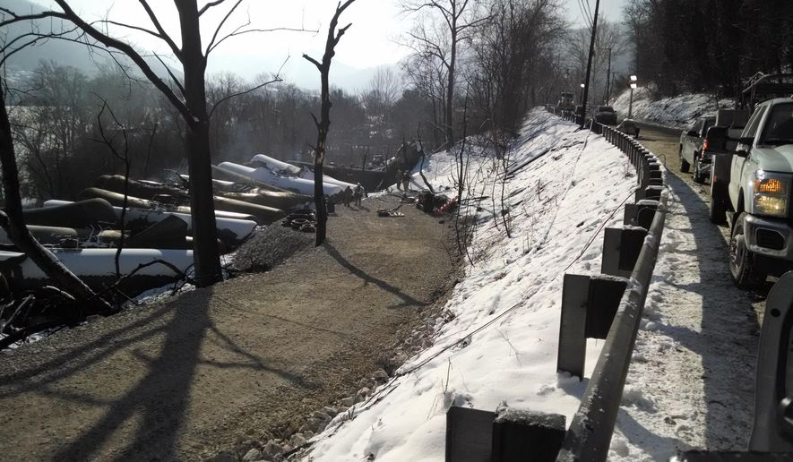 The wreckage of an oil train derailment in Mount Carbon, W.Va., sits by the road on Friday, Feb. 20, 2015. One lane of a road leading to the derailment site has been opened.  Investigators are trying to determine what caused the derailment of the train carrying 3 million gallons of crude from North Dakota's Bakken oil fields to an oil-shipping depot in Yorktown, Virginia. Crews still must remove damaged tank cars from the scene.  (AP Photo/Bob Aaron, WCHS-TV) (AP Photo/WCHS-TV, Bob Aaron)