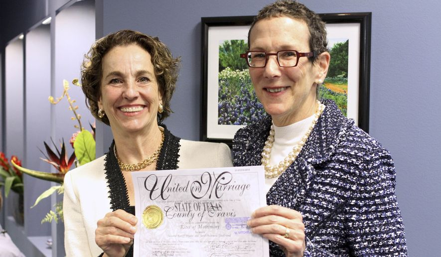 Suzanne Bryant (left) and Sarah Goodfriend hold up their marriage license after a press conference on Thursday afternoon. They became the first same-sex couple to marry in Texas on Thursday morning. (AP Photo/The Daily Texan, Mariana Mu)