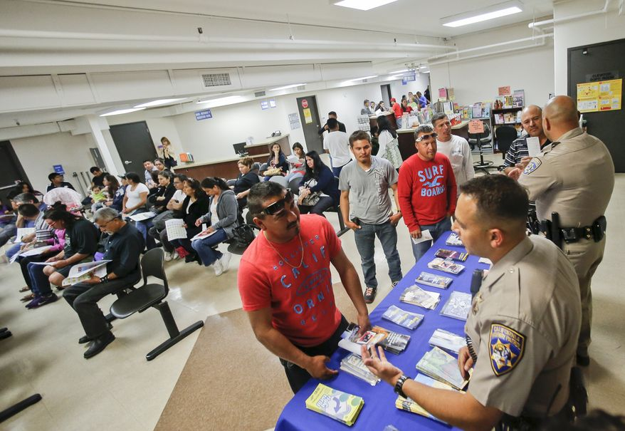 In this April 23, 2014, file photo, California Highway Patrol officers Armando Garcia, right, and Ray Patton talk with immigrants attending an information session at the Mexican Consulate regarding obtaining a California drivers license in San Diego. California issued 59,000 driver's licenses to immigrants who are in the country illegally during the first month their applications were accepted, state officials said Wednesday, Feb. 18, 2015. Overall, a total of about 236,000 immigrants in the country illegally began the application process during January, the state Department of Motor Vehicles said in a statement. (AP Photo/Lenny Ignelzi, File)