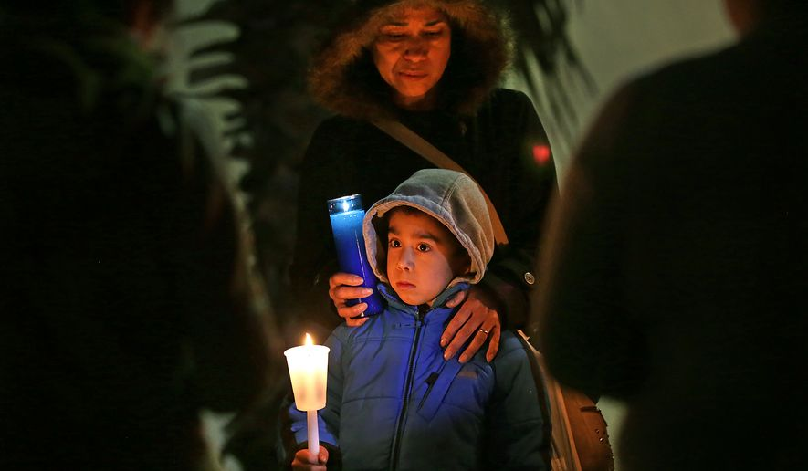 In this Feb. 17, 2015 photo, Clementina Herrera comforts her son Luis Manuel Herrera, 6, who's father is in Ciudad Juarez, as he explains that he believes God will make it so his family can be together at a rally for immigration reform in front of Devine Redeemer Presbyterian Church sponsored by the Texas Organizing Project in San Antonio, Texas. Immigrants across the country expressed disappointment Tuesday after a federal judge put a hold on President Barack Obama's plan to protect more than 4 million people living illegally in the U.S. from deportation. But many said they haven't lost hope. (AP Photo/The San Antonio Express-News, Bob Owen)