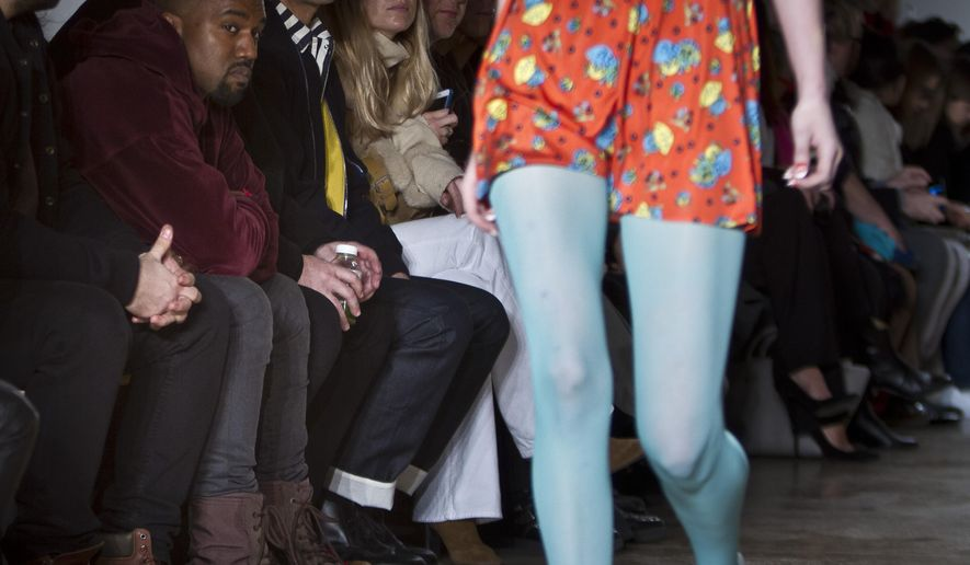 Kanye West, second from left, watches as a model walks the runway during the presentation of the Jeremy Scott Fall 2015 collection at Fashion Week, Wednesday, Feb. 18, 2015, in New York. (AP Photo/Bebeto Matthews)