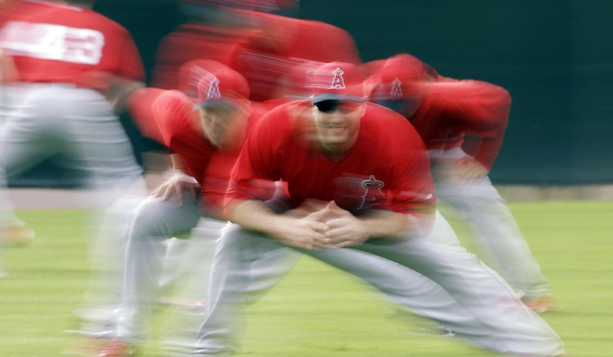 Los Angeles Angels players run a drill during a spring training baseball workout Friday, Feb. 20, 2015, in Tempe, Ariz. (AP Photo/Morry Gash)