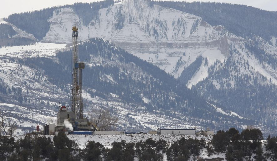 In this photograph taken Thursday, Feb. 28, 2013, near Parachute, Colo., the drill rig at a natural gas site stands with mountains in the background on Colorado's Western Slope. A campaign to get universities to stop investing in greenhouse gas-producing fuels has come deep into energy country as activists will ask the University of Colorado to divest from coal and peteroleum companies. (AP Photo/David Zalubowski)