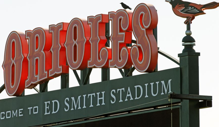 A bird perches on the scoreboard in the outfield of Ed Smith Stadium, the spring training home of the Baltimore Orioles before a baseball spring training workout  in Sarasota, Fla., Friday, Feb. 20, 2015.  (AP Photo/Gene J. Puskar)