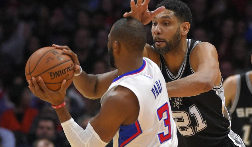 San Antonio Spurs forward Tim Duncan, right, hits Los Angeles Clippers guard Chris Paul in the head as Paul passes the ball during the first half of an NBA basketball game Thursday, Feb. 19, 2015, in Los Angeles. (AP Photo/Mark J. Terrill)