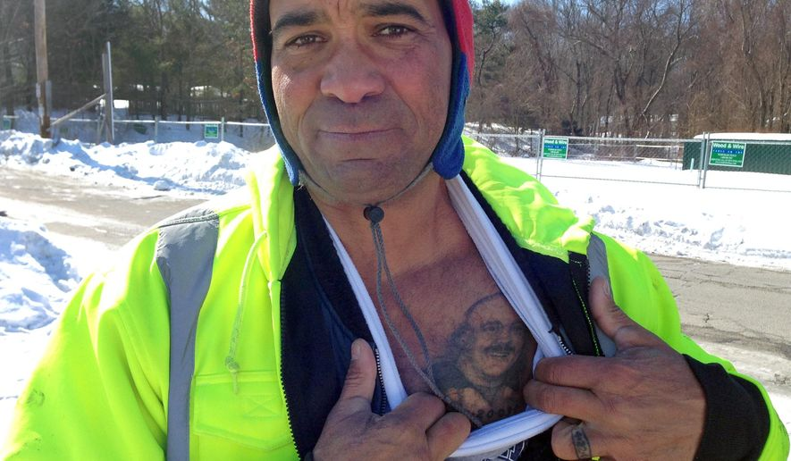 Jody King of Warwick, R.I. displays a tattoo of his brother, Tracy, a bouncer at The Station nightclub who was among 100 people killed in a 2003 fire at the club in West Warwick, as snow blankets the site on Friday, Feb. 20, 2015. Relatives of the 100 people who died in a fire at the nightclub were quietly marking the 12th anniversary of the disaster on Friday as they continue to raise funds for a permanent memorial. (AP Photo/Amy Anthony)