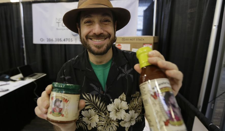 "Eric Schneider, owner of ""The Sauce Guy"" barbecue sauce company, poses for a photo holding both the standard version of his sauce at right, and a new version that is infused with marijuana hash oil, at left, Thursday, Feb. 19, 2015, at CannaCon, a marijuana business trade show in Seattle featuring exhibitors offering everything from grow lights to exotic pot seeds. (AP Photo/Ted S. Warren)"