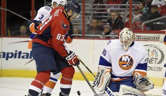 Washington Capitals center Jay Beagle (83) battles for the puck against New York Islanders goalie Chad Johnson (30) and Travis Hamonic (3) during the second period of an NHL hockey game, Saturday, Feb. 21, 2015, in Washington. (AP Photo/Nick Wass)