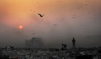 A blanket of smoke filters the setting sun as young ragpickers search for reusable material at a garbage dump in New Delhi. India and a host of other countries are demanding payments as part of the Paris Agreement to reduce their levels of pollution. (Associated Press/File)