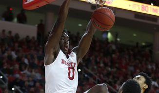North Carolina State's Abdul-Malik Abu (0) slams for two points as Virginia Tech's Justin Bibbs (10) watches during the first half of an NCAA college basketball game in Raleigh, N.C., Saturday, Feb. 21, 2015. (AP Photo/The News & Observer, Ethan Hyman) MANDATORY CREDIT