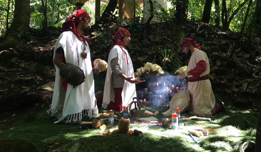 """In this Feb. 9, 2015 photo, hip-hop musicians Yefrey Pacheco, left, Rene Dionisio a.k.a. Tz´utu Baktun Kan, center, and Juan Martinez a.k.a. """"Dr. Native"""" perform a Mayan ritual at the base of the San Pedro Volcano in San Pedro Atitlan, Guatemala. The band, Balam Ajpu, which means Jaguar Warrior or Warrior of Light, raps in the ancient Mayan Tz'utujil language.  """"Since the time of the (Spanish) invasion, the (Mayan) worldview was persecuted, even almost snuffed out, but now it's returning to life, relying on music and sustaining itself in art,"""" said Dionisio. """"Our commitment as artists is to rescue the ancient art."""" (AP Photo/Sonia Perez)"""
