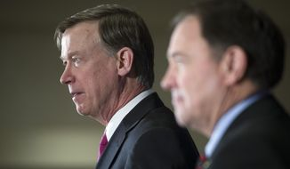 National Governors Association Chairman, Colorado Gov. John Hickenlooper, left, accompanied by Vice Chair, Utah Gov. Gary Herbert, conduct the opening news conference of the National Governors Winter Meeting in Washington, Saturday, Feb. 21, 2015. (AP Photo/Cliff Owen)