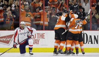 Philadelphia Flyers' Chris VandeVelde (76), Jakub Voracek (93), of the Czech Republic, and Braydon Coburn (5) celebrate with Michael Del Zotto as Washington Capitals' Eric Fehr (16) kneels on the ice Del Zotto's go-ahead goal during the third period of an NHL hockey game, Sunday, Feb. 22, 2015, in Philadelphia. Philadelphia won 3-2. (AP Photo/Matt Slocum)