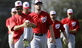 Washington Nationals pitcher Gio Gonzalez, left, stretches with teammates during a spring training baseball workout, Sunday, Feb. 22, 2015, in Viera, Fla. (AP Photo/David Goldman)