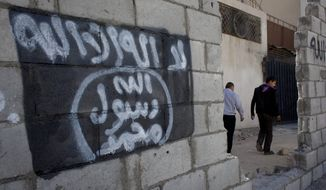 "Two Jordanian men walk past graffiti depicting the flag of the Islamic State group with Arabic that reads, ""There is only one God and Muhammad is his prophet,"" in the city of Ma'an, Jordan. (Associated Press)"