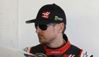 In this Wednesday, Feb. 18, 2015, photo, Kurt Busch stands in his garage during a practice session for the Daytona 500 NASCAR Sprint Cup Series auto race at Daytona International Speedway, in Daytona Beach, Fla. (AP Photo/Terry Renna)