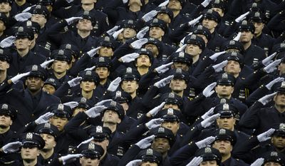 New recruits raise their heads and salute in honor of deceased officers Rafael Ramos and Wenjian Liu during a New York Police Academy graduation ceremony, Monday Dec. 29, 2014, at Madison Square Garden in New York. Nearly 1000 officers were sworn in as tensions between city hall and the NYPD continued following the Dec. 20 shooting deaths of officers Ramos and Liu. (AP Photo/John Minchillo)